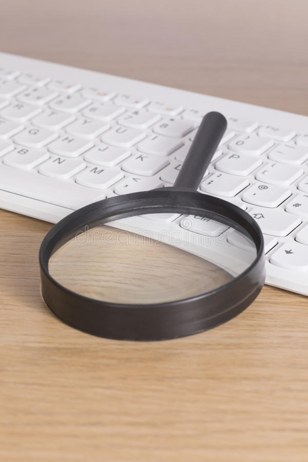 Magnifying glass on PC keyboard. Magnifying glass of black plastic laying over white PC keyboard on wooden desk, close-up from high angle royalty free stock images