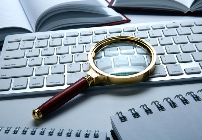 Magnifying glass on the pc keyboard search technology. Concept stock photography