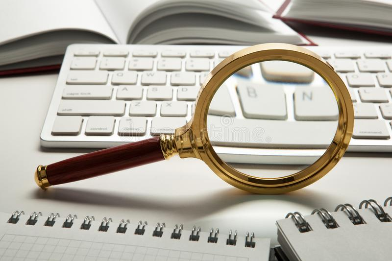 Magnifying glass on the pc keyboard search technology. Concept royalty free stock image