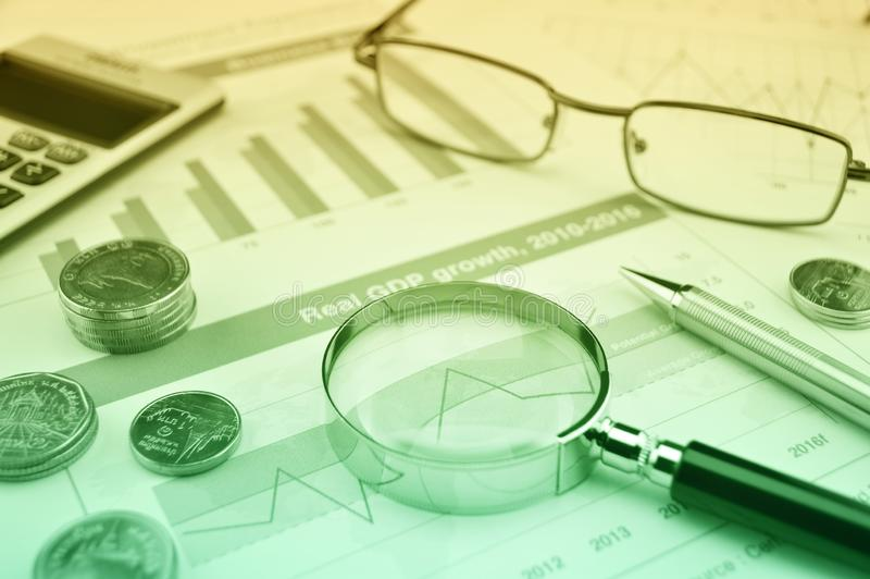 Magnifying glass, pen, coins, calculator and glasses on growth financial graph, Business success concept stock photography