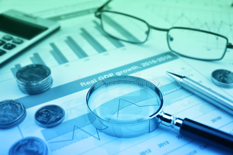 Magnifying glass, pen, coins, calculator and glasses on growth financial graph, Business success concept stock photos