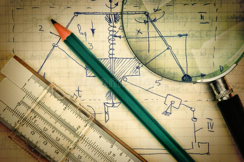 Magnifying glass and a slide rule on the old page. With the calculations in mechanics stock images