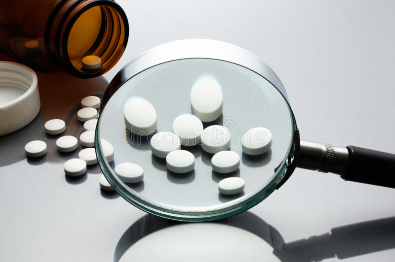 Magnifying glass, tablets and bottle on gray reflection background. Checking ingredients and effectiveness of medicine stock photo