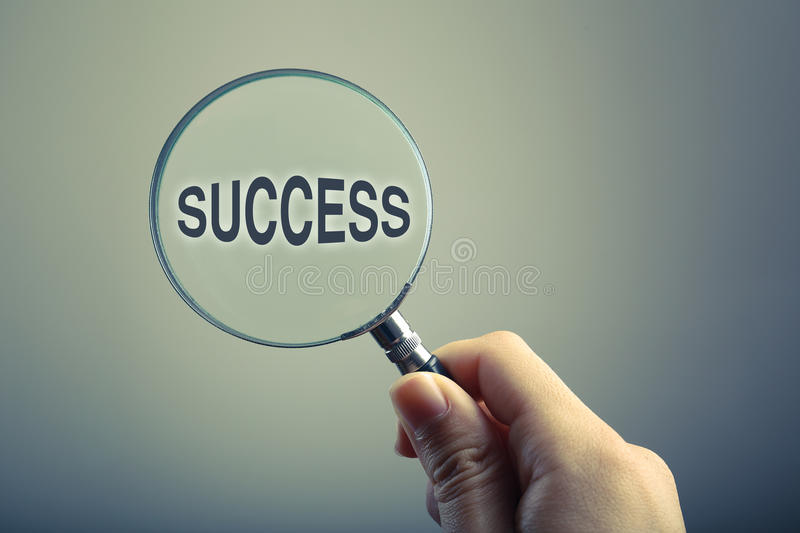 Magnifying Glass With Text Success. Hand holding a magnifying glass with text Success stock photo