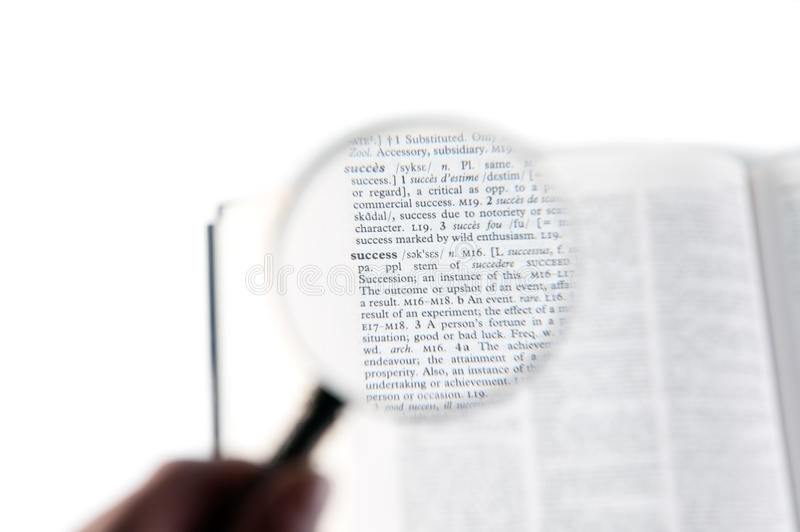 A magnifying glass on the word success. On a dictionary royalty free stock images