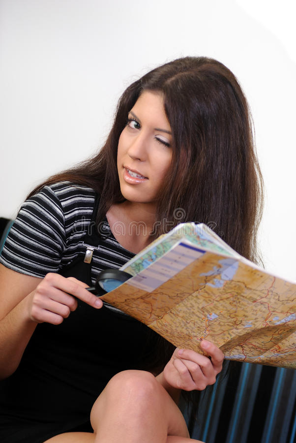 Magnifying len and a map. Woman Looking Through A Magnifying Lens to a map stock photo