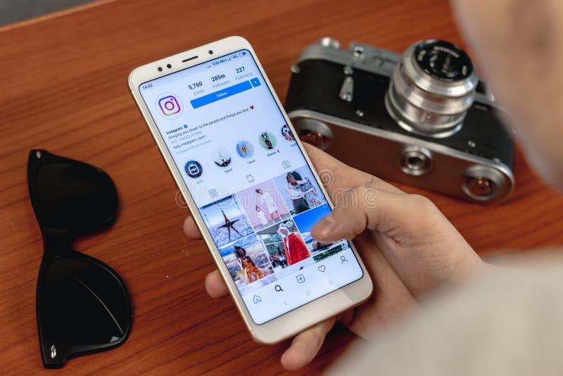 Magnitogorsk, Ρωσία - 14 Μαρτίου 2019: Ένας νεαρός άνδρας κρατά ένα smartphone με μια ανοικτή εφαρμογή instagram και στοκ φωτογραφία