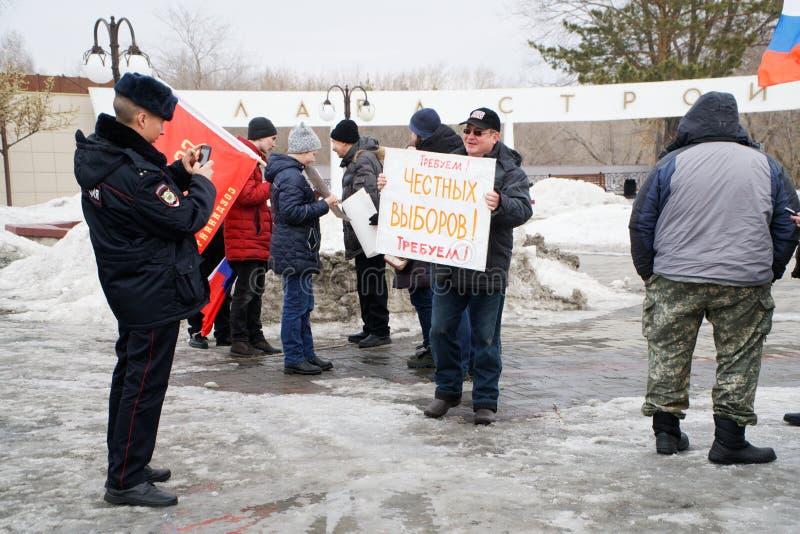 Magnitogorsk, Rosja, - Marzec, 10, 2019 Protestacyjny spotkanie dla bezpłatnego interneta Policjant bierze obrazki jeden uczestni obrazy royalty free