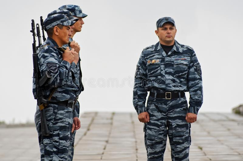 Magnitogorsk, Rusia, - agosto, 2, 2014 Oficiales de policía con las ametralladoras en una calle de la ciudad durante la niebla fotografía de archivo