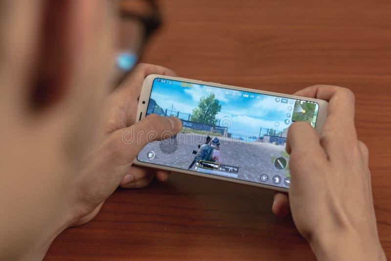 Magnitogorsk, Rusia - 14 de marzo de 2019: Un hombre joven juega el móvil de Pubg: El móvil de los campos de batalla de PlayerUnk fotografía de archivo libre de regalías