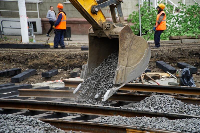 Magnitogorsk, Rusia, - mayo, 17, 2019 El cubo del excavador enterrado en escombros reparó los carriles de la tranvía Cruces de Ma fotografía de archivo