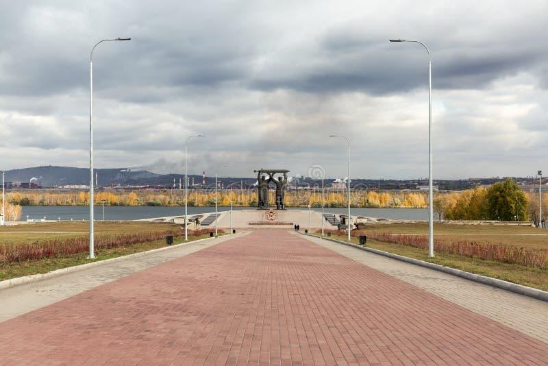 MAGNITOGORSK, RUSIA - OCTUBRE DE 2018: Monumento Posterior-delantero una escultura famosa grande y una llama eterna en flor del g imágenes de archivo libres de regalías