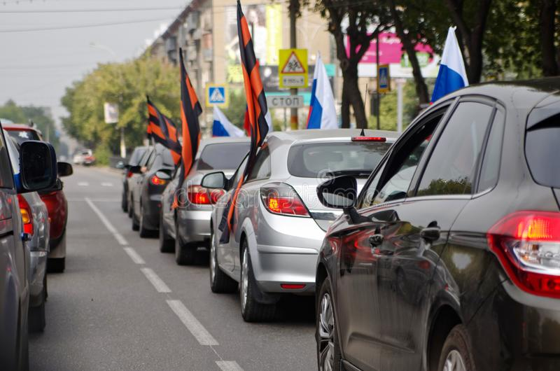 Magnitogorsk, Russia, - August, 22, 2014. A group of cars with Russian and St. George flags on a city street stock photo