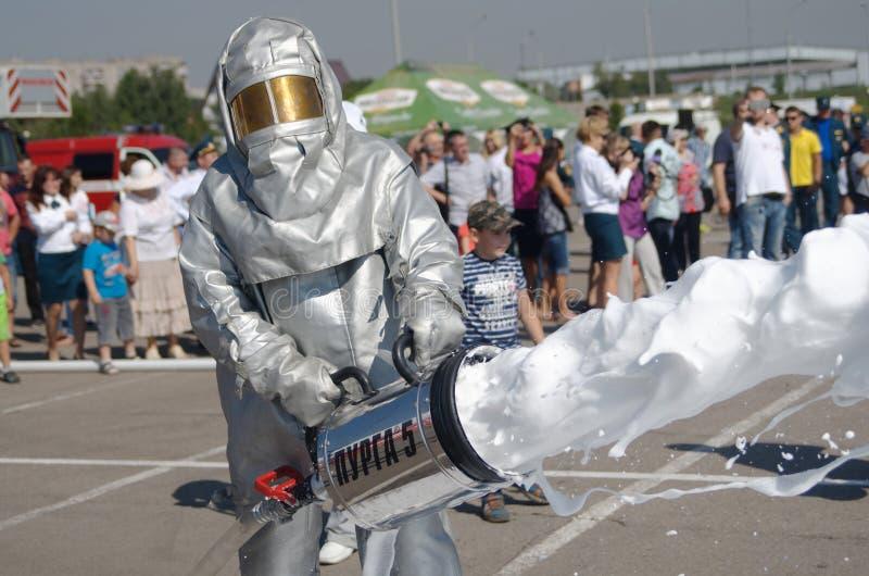 Magnitogorsk, Russia, - augusta, 7, 2014 Il pompiere mette fuori un fuoco nella piazza Vestito protettivo e schiuma per immagini stock libere da diritti