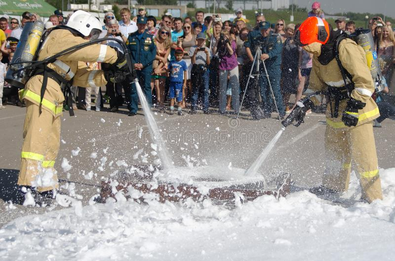 Magnitogorsk, Russie, - août, 7, 2014 Deux sapeurs-pompiers dans les tenues de protection s'éteignent un pneu de voiture brûlant  image libre de droits