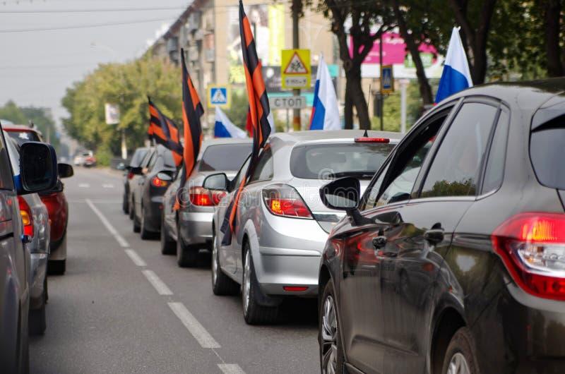Magnitogorsk, Russie, - août, 22, 2014 Un groupe de voitures avec des drapeaux de Russe et de St George sur une rue de ville photo stock
