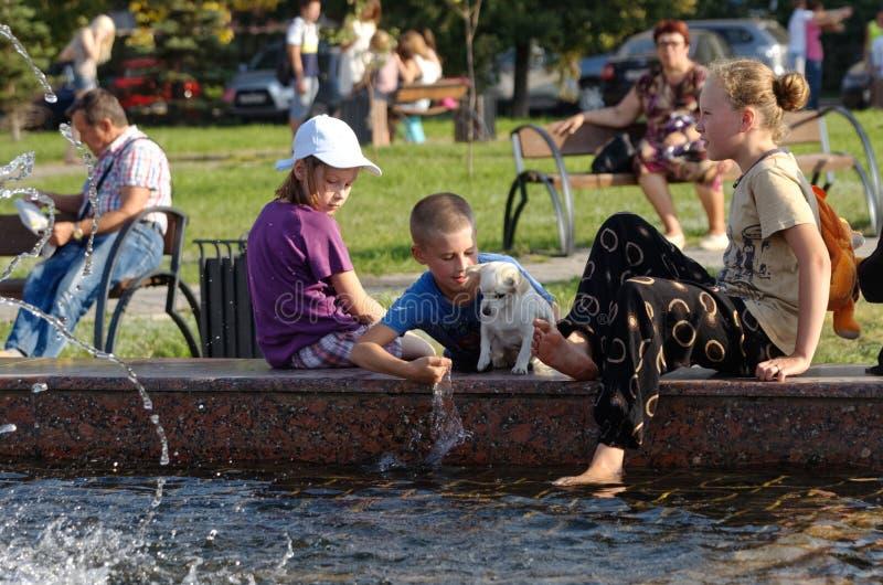 Magnitogorsk Ryssland, - Augusti, 22, 2014 Barn och hundkapplöpningen spelar nära springbrunnen i stadfyrkanten royaltyfria bilder