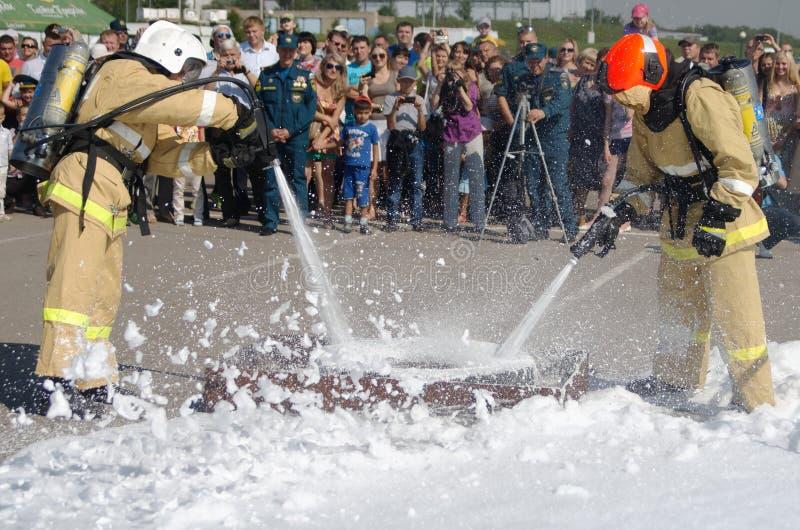 Magnitogorsk Ryssland, - Augusti, 7, 2014 Två brandmän i skyddande dräkter släcker ett bilgummihjul som bränner i stadfyrkanten royaltyfri bild