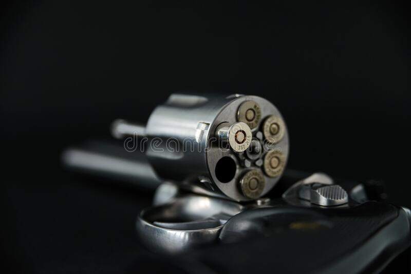 357 magnum caliber revolver pistol, cylinder open with bullets protruding from the gun.  stock photo
