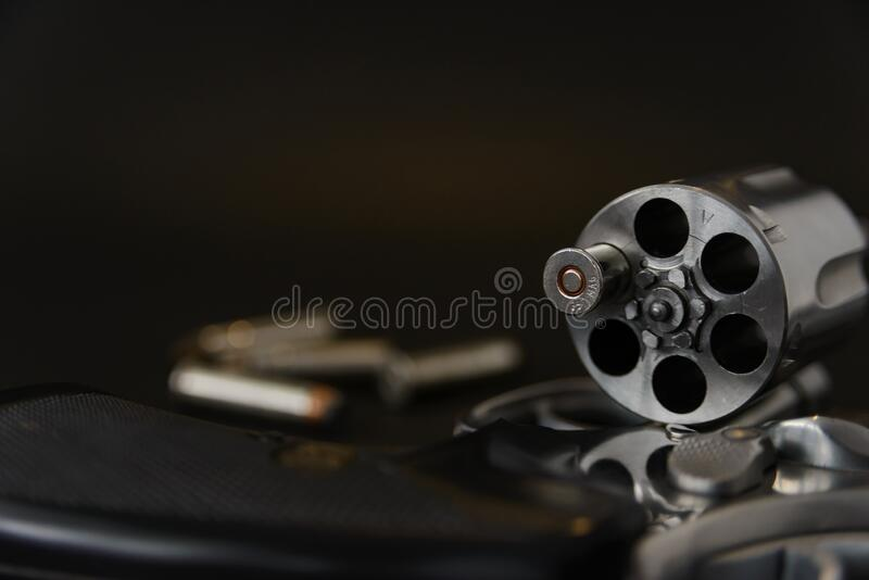 357 magnum caliber revolver pistol, cylinder open with a single bullet protruding from the gun.  royalty free stock image