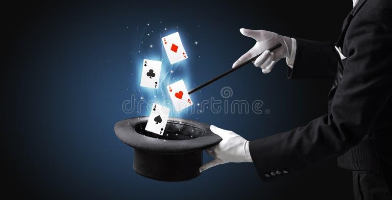 Mago che fa trucco con la bacchetta e le carte da gioco immagini stock libere da diritti