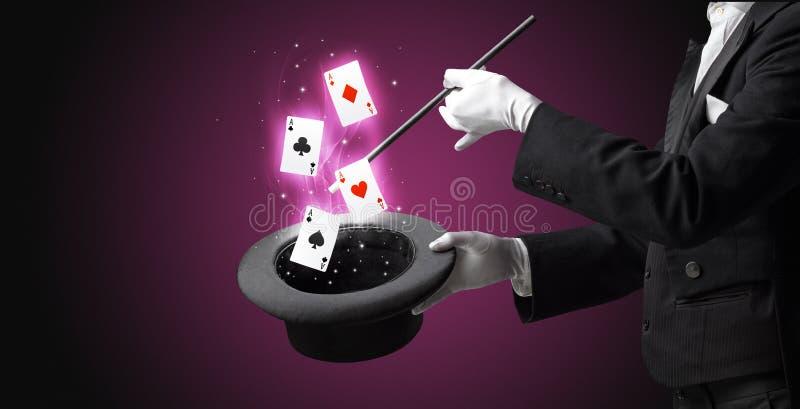Mago che fa trucco con la bacchetta e le carte da gioco immagine stock