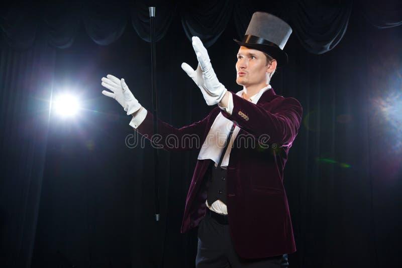 Mago con la bola al aire, hombre del juglar, persona divertida, magia negra, foco de la ilusión A con un bastón que eleva y manti fotografía de archivo libre de regalías