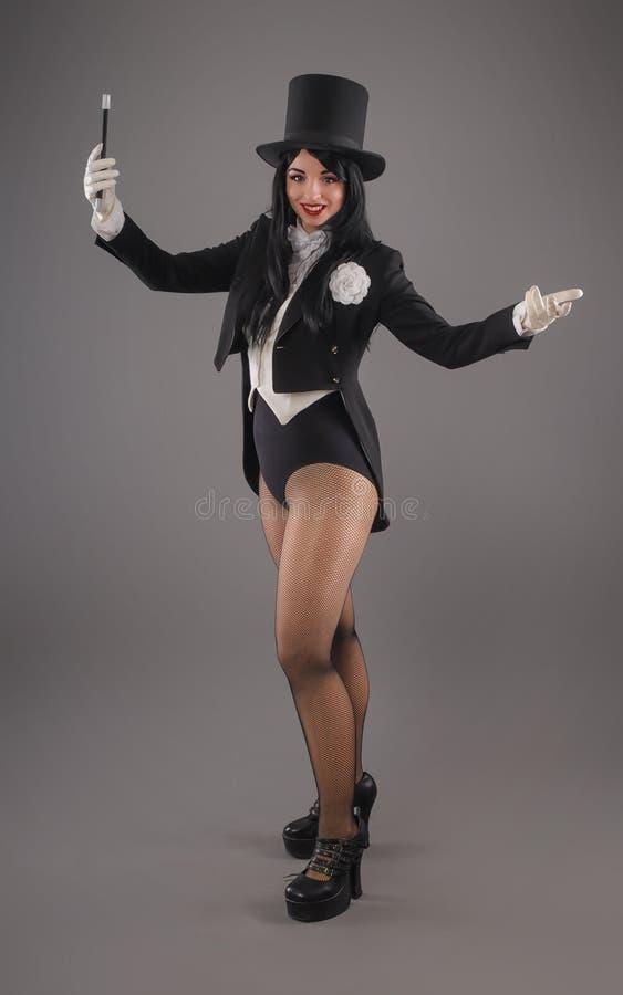 Mago de sexo femenino en traje del traje con el palillo mágico que hace truco foto de archivo libre de regalías