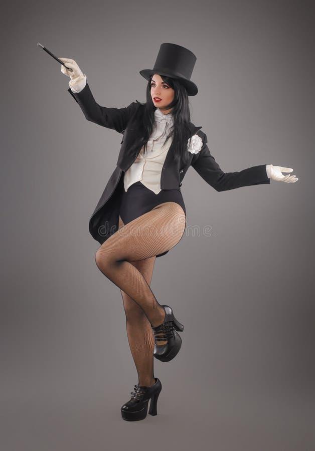 Mago de sexo femenino en traje del traje con el palillo mágico que hace truco fotos de archivo