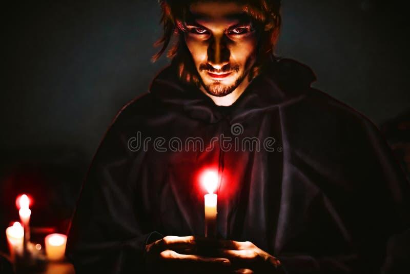 Mago diabolico con una candela fotografia stock