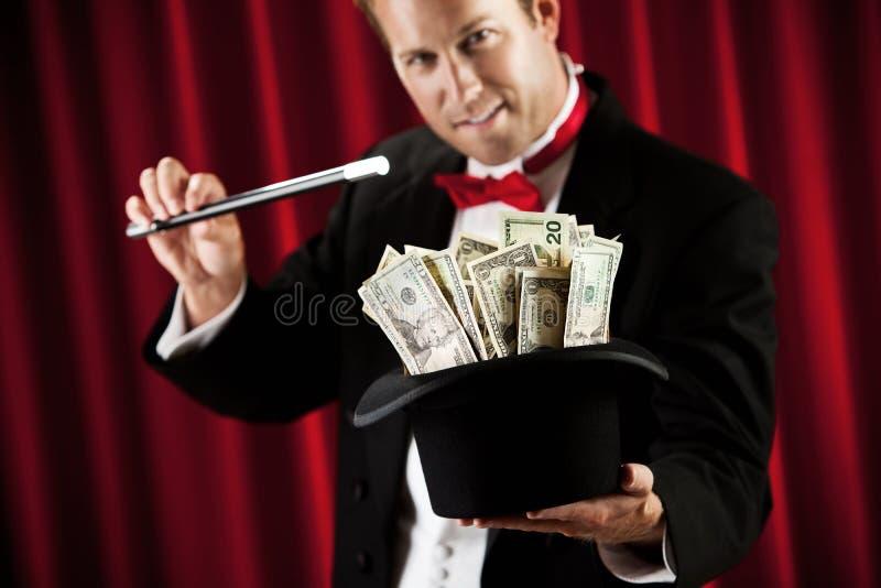 Mago: Haciendo un truco con el sombrero lleno de dinero imagen de archivo