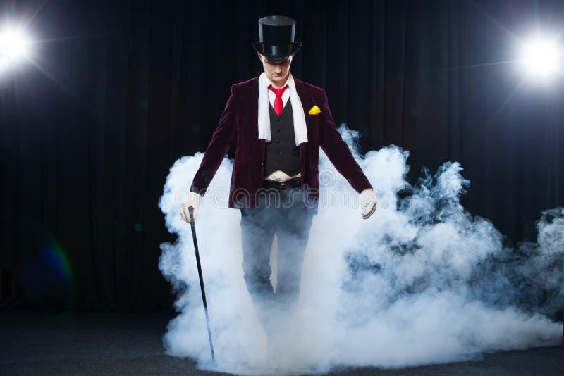 Mago, hombre del juglar, persona divertida, magia negra, ilusión que se coloca en la etapa con un bastón de la luz hermosa imagenes de archivo