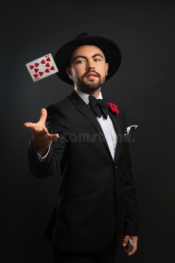 Mago maschio che mostra i trucchi con la carta su fondo scuro immagini stock