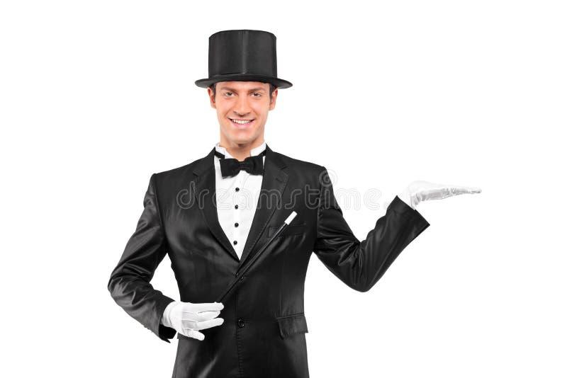 Mago que desgasta el sombrero superior con la mano izquierda levantada fotografía de archivo libre de regalías