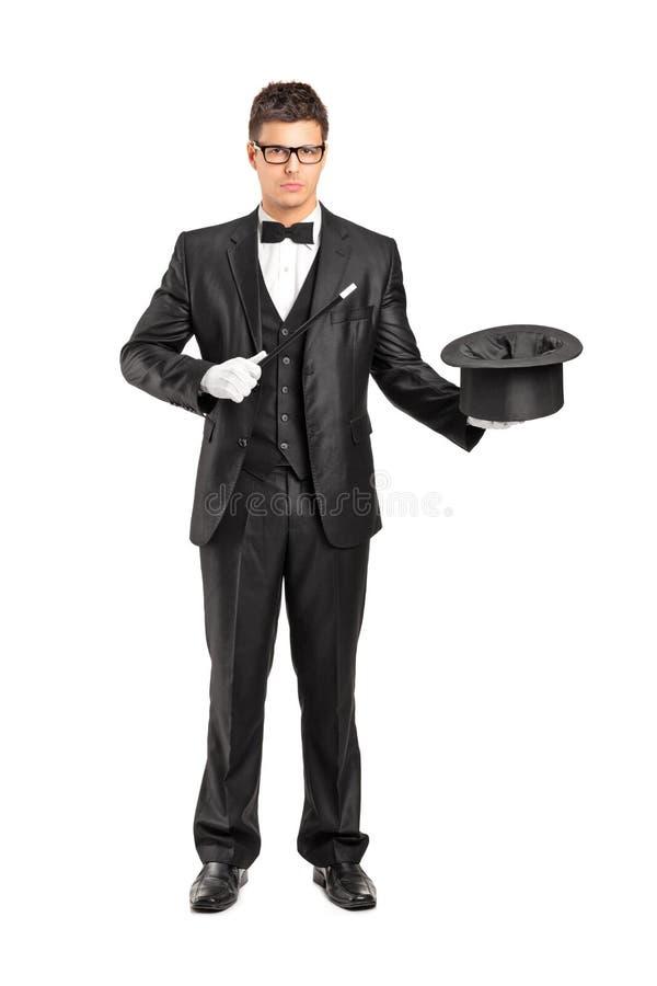 Mago que sostiene una varita mágica y un sombrero superior fotografía de archivo