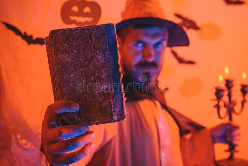 Mago sabio divertido en un fondo de Halloween Mago, hechicero, brujo Hombre hermoso en el sombrero del traje del mago para Hallow fotografía de archivo