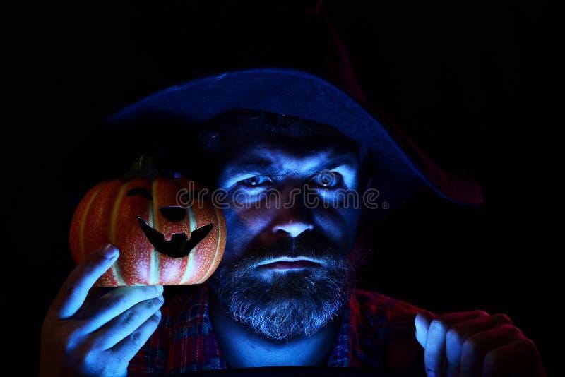 Mago sabio divertido en un fondo de Halloween Mago, hechicero, brujo Misterio y concepto del horror Linterna de Gato o foto de archivo libre de regalías
