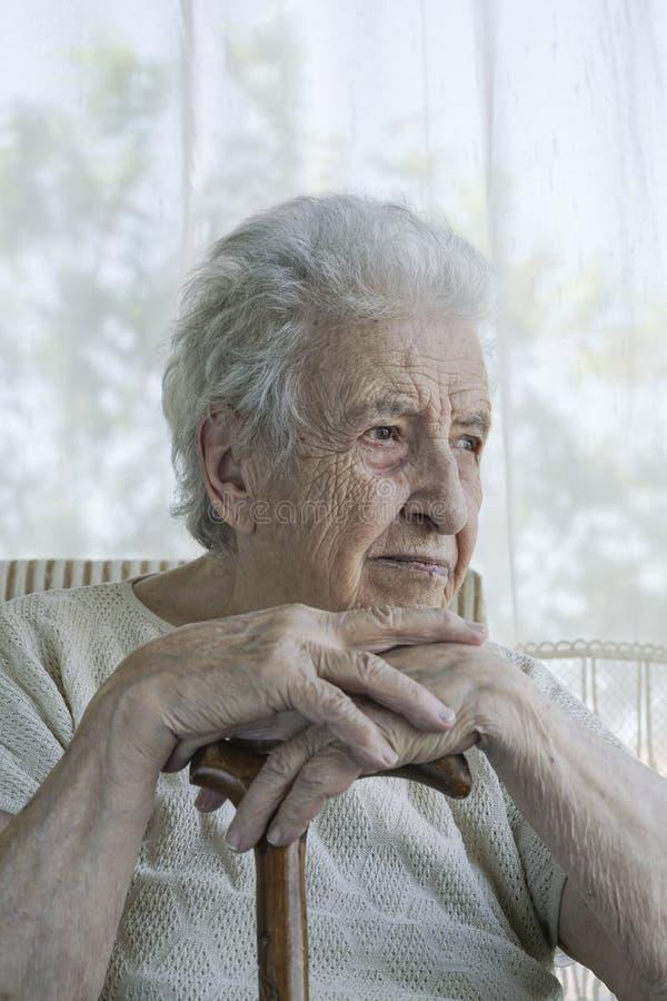 Magra senior della donna dentro su una canna di legno a casa fotografie stock libere da diritti