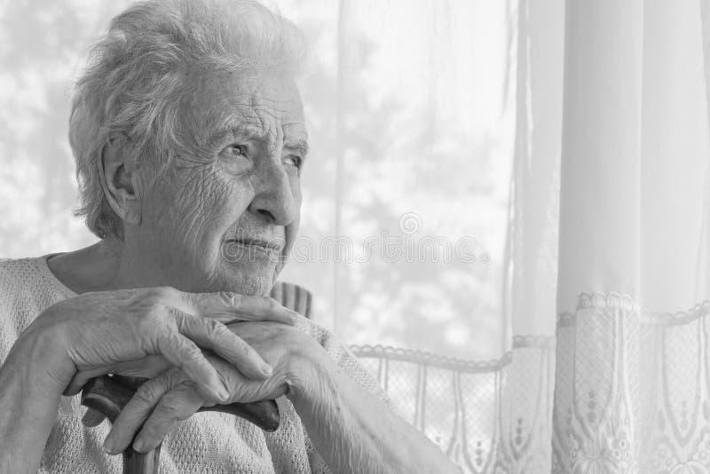 Magra senior della donna dentro su una canna di legno a casa immagini stock