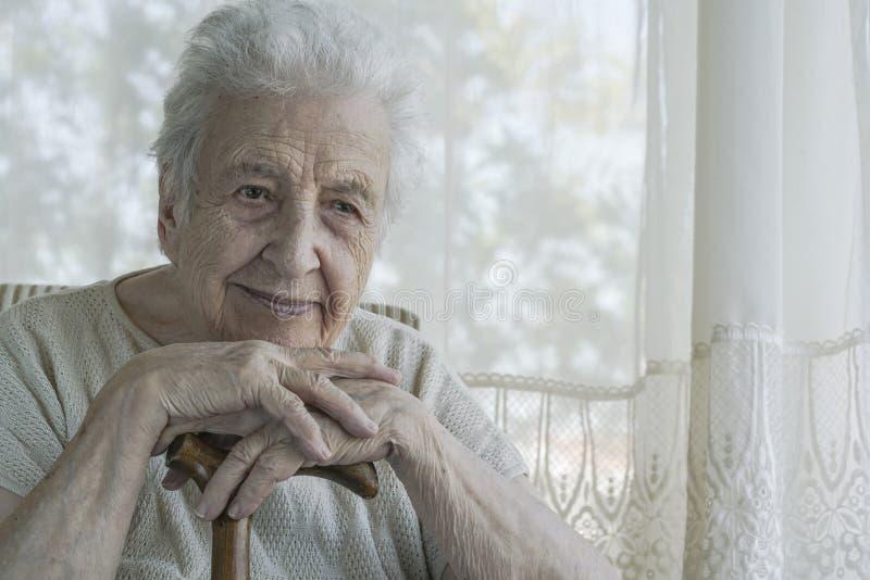Magra senior della donna dentro su una canna di legno a casa fotografia stock