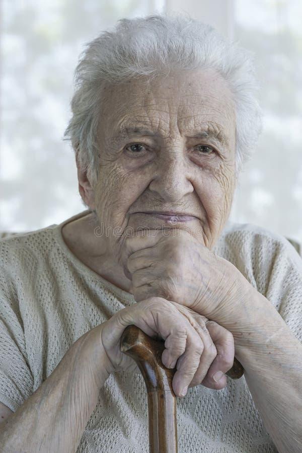 Magra senior della donna dentro su una canna di legno a casa fotografia stock libera da diritti