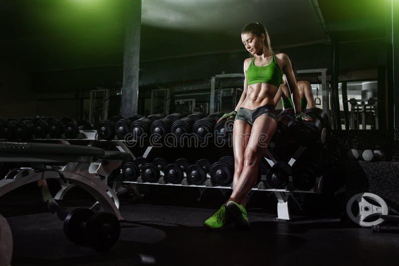Magro atractivo de la muchacha del atleta en fila de la pesa de gimnasia en gimnasio foto de archivo