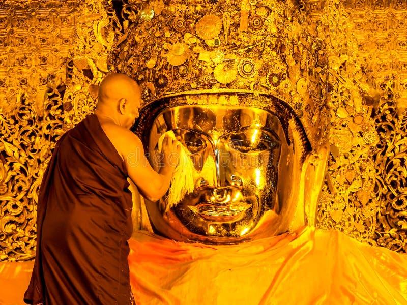 Mahamuni Buddha image face wash ritual, Mandalay, Myanmar 6. MANDALAY-MAY23: The senior monk wash the face of Hahamuni Buddha image in ritual of the Buddha image stock photography
