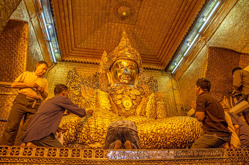 Mahamuni Buddha Temple. MANDALAY - FEBRUARY 26: Buddhist believers venerated Buddha statue and sticking golden leaves at Mahamuni Buddha temple on February 26 royalty free stock image