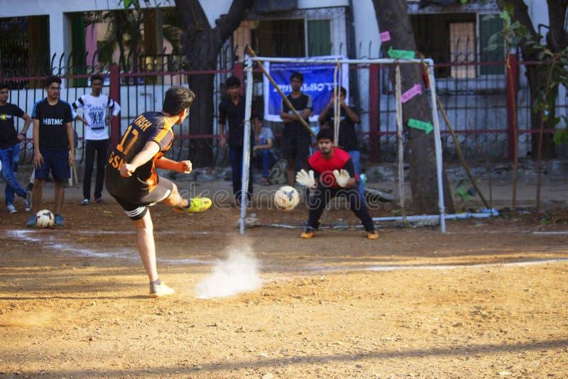 MAHARASHTRA, ÍNDIA, em fevereiro de 2019, meninos de Yong que batem o pontapé de grande penalidade durante o fósforo de futebol imagem de stock