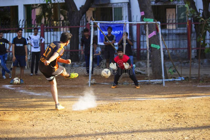 MAHARASHTRA, INDIA, February 2019, Yong boys hitting penalty kick during football match.  stock image