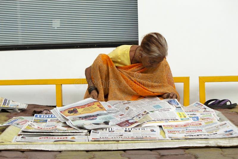 MAHARASHTRA INDIEN, mars 2018, gammal kvinna som säljer och läser tidningar arkivfoton
