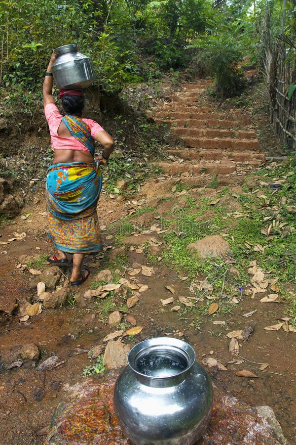 MAHARASHTRAEN INDIEN, April 2013, kvinna bär ett vatten från en ström royaltyfria bilder