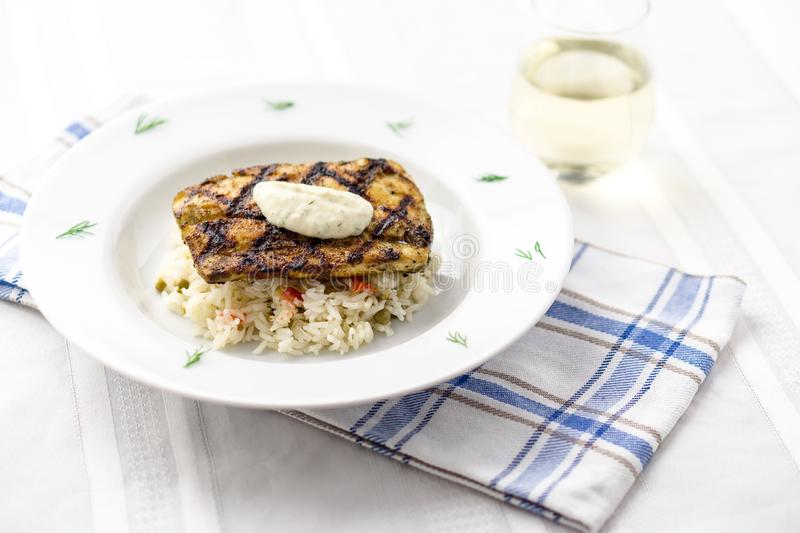 Mahi mahi grilled fish with rice and wine. This lean tropical white fish is also known as common dolphinfish or dorado. Considered an healthy food rich in stock photography