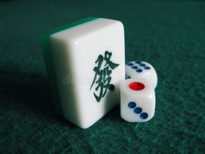 Mahjong and dice. Mahjong tile of rich and dice on gamble table royalty free stock photos
